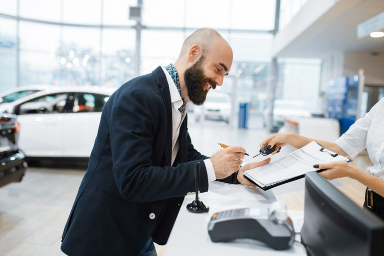 Man signs a contract in car dealership